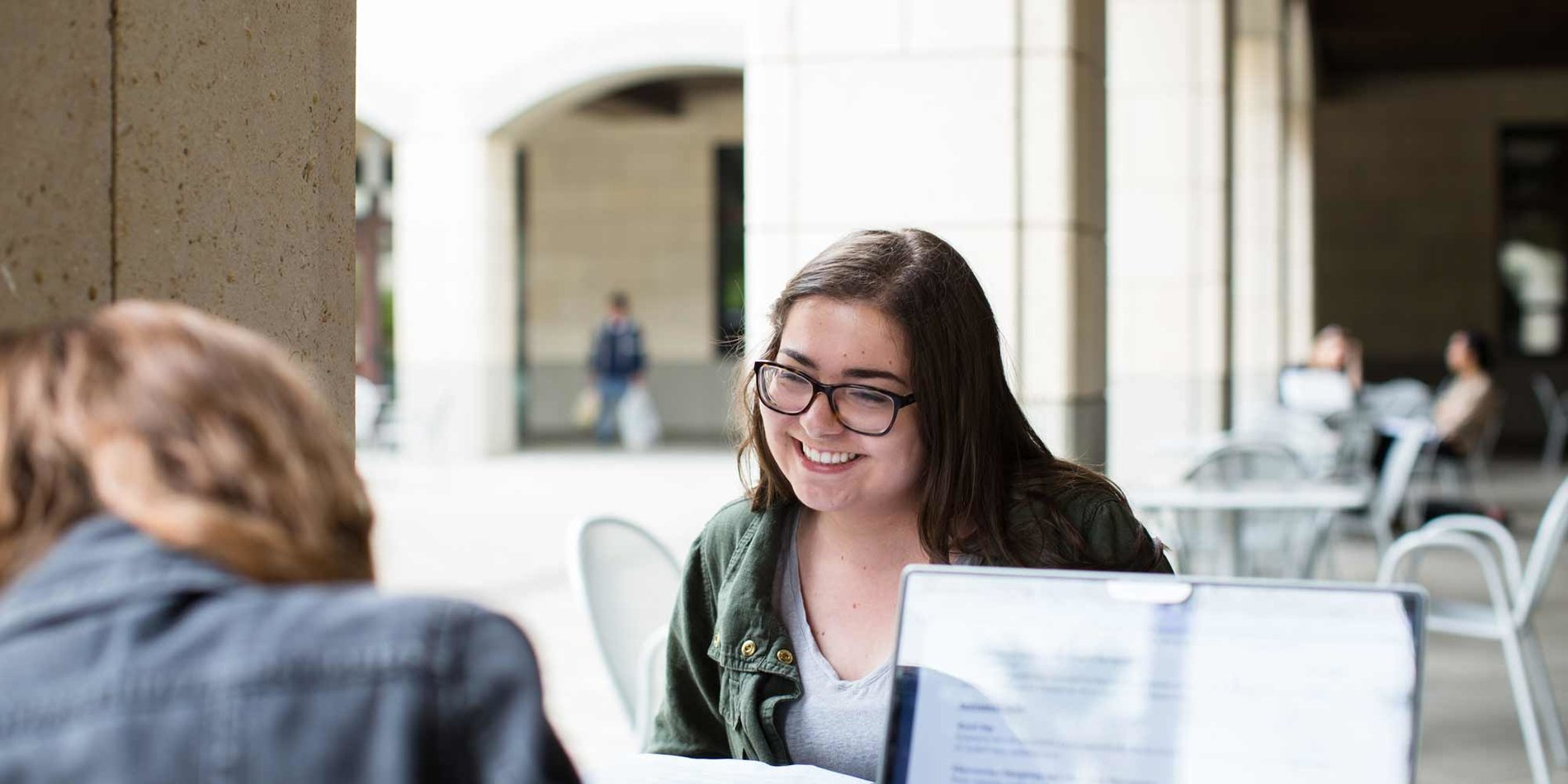 A female student smiles at her coworker across the table outside Forbes Cafe in the Stanford Engineering Quad